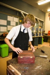 A student fabricates a box in woodworking class.
