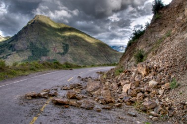 A landslide of rocks has partially covered this road.