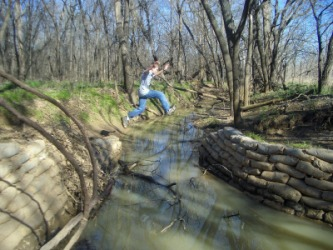 A boy leaps across a stream.