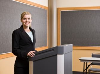 A woman standing at a lectern.