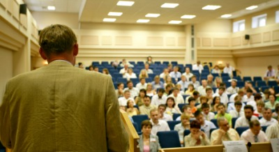 A group of  people listening to a lecturer.