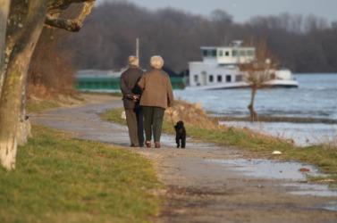 A couple take a leisurely walk around a lake.
