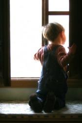 This child has knelt on a window seat.