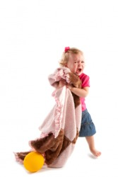 An unhappy child hugs her security blanket.