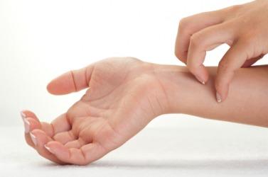A woman scratches her wrist.