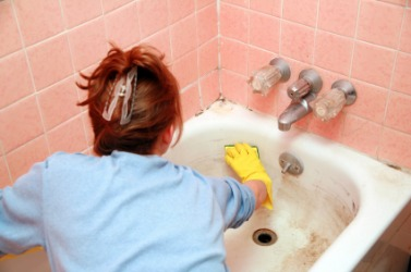 A woman scrubs  her bathtub.