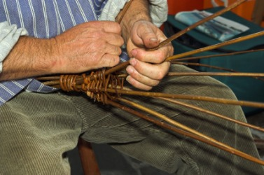 A man engaged in the craft of basketry.