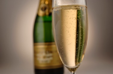 A bottle and single glass of champagne wine.
