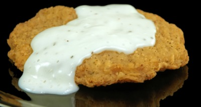 A piece of chicken-fried steak with gravy.