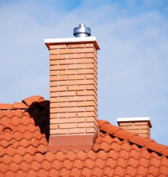 A brick chimney on a tiled roof.
