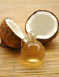 A bottle of coconut oil with two coconut halves.