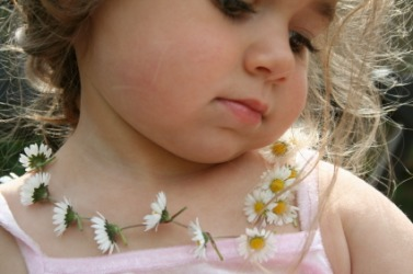 A little girl wearing a daisy chain.