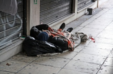 A destitute man sleeps on the street.