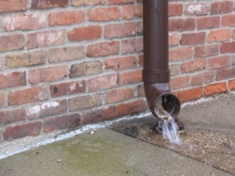 Water running out of a drainpipe.