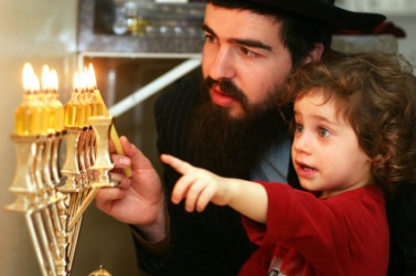 A child watches his father light the menorah to celebrate Hanukkah.