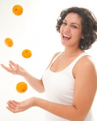 A woman juggles tangerines.