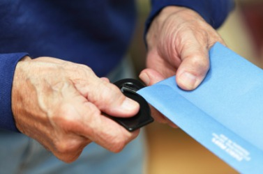 A man using a paper knife to open an envelope.