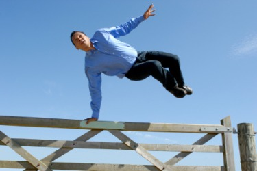 A man vaults over a gate.