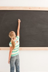 A girl writing on a chalkboard.