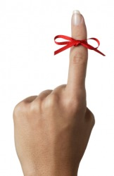 A womans hand with a red ribbon tied around one digit.