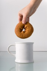 A hand about to dip a donut into a cup of coffee.