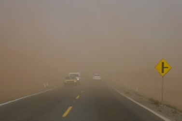 A road nearly hidden by a dust storm.