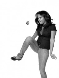A woman playing with a footbag.
